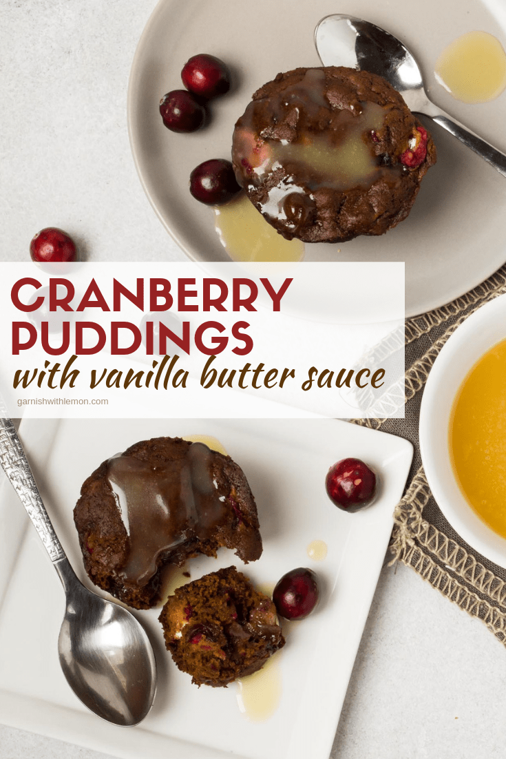Top down image of Cranberry puddings with Vanilla butter sauce on a white plate with fresh cranberries for garnish.