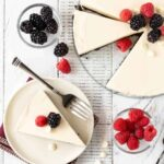 Top down Image of white chocolate tart recipe on white background with fresh raspberries and blackberries for garnish.