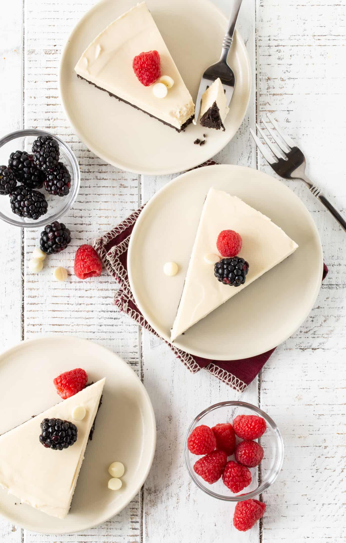 Top down image of 3 slices of Easy White Chocolate Tart recipe on white plates with fresh berries for garnish.