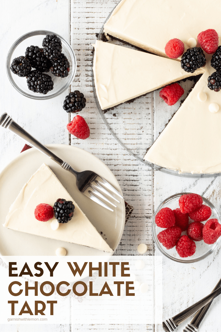 Pinterest Image of Easy White Chocolate Tart recipe with slices on white paltes and fresh berries for garnish.