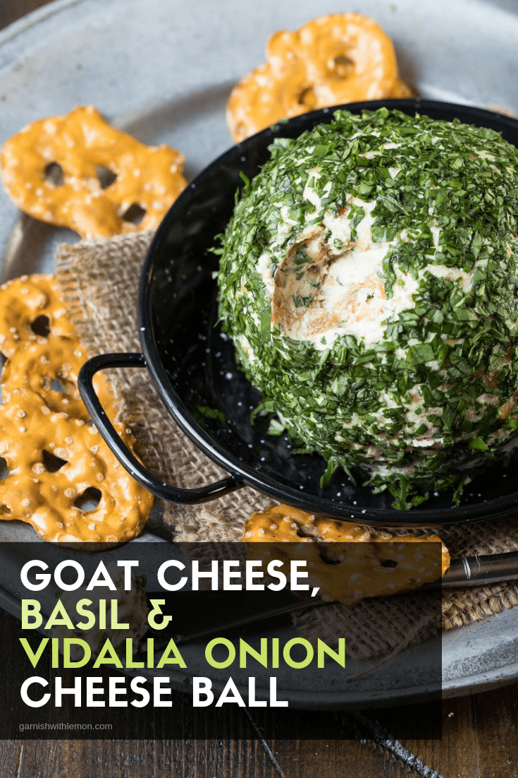 Top down image of Goat Cheese, Basil and vidalia Onion Cheese ball on a silver tray with pretzels.