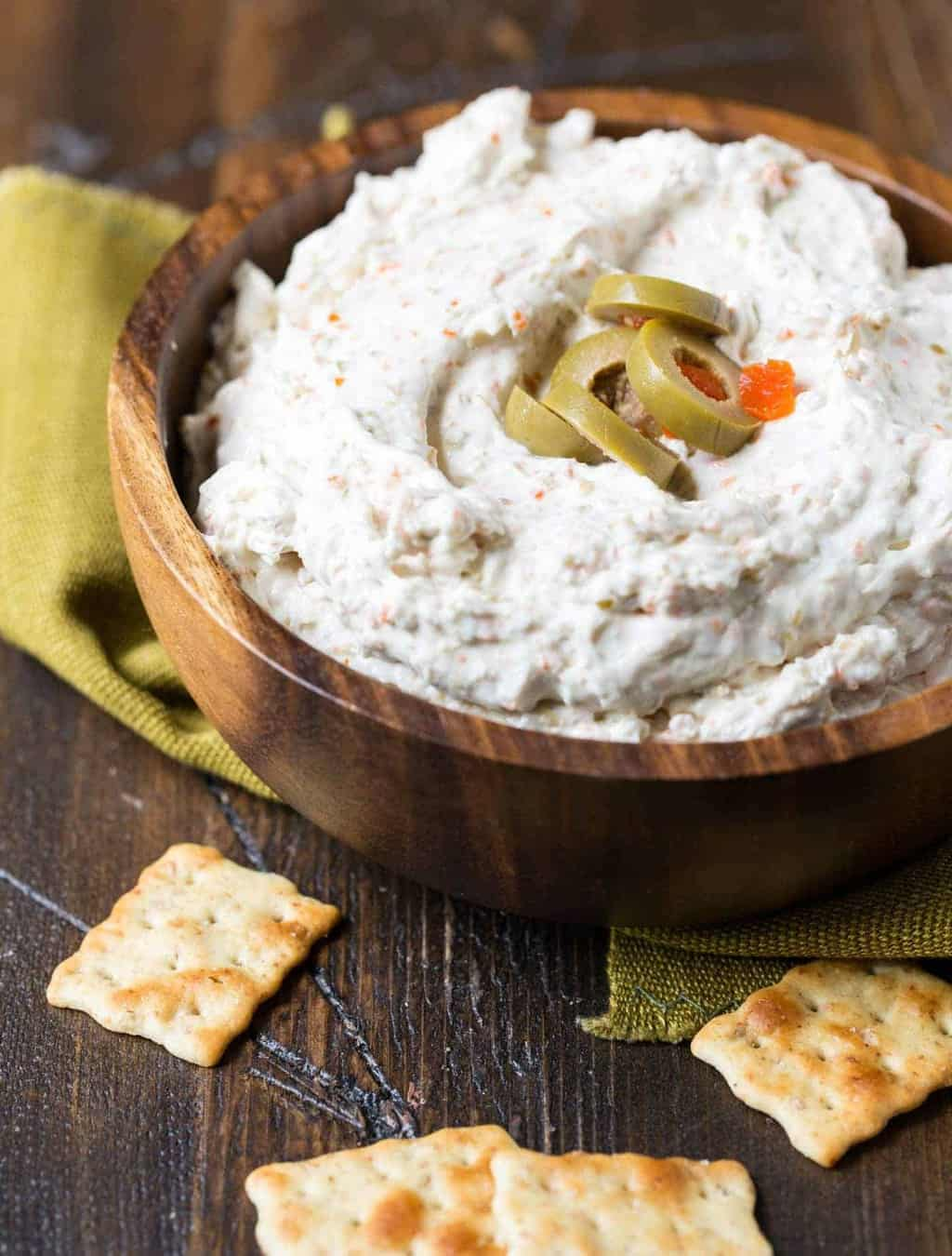 Close up of green olive dip in wooden bowl with crackers and sliced olives.