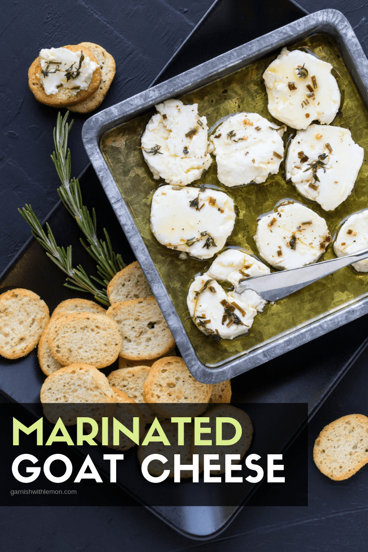 Top down image of marinated goat cheese recipe in silver tray with bread for dipping.