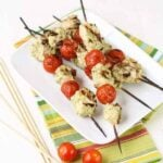 A plate of chicken and tomato kebabs.