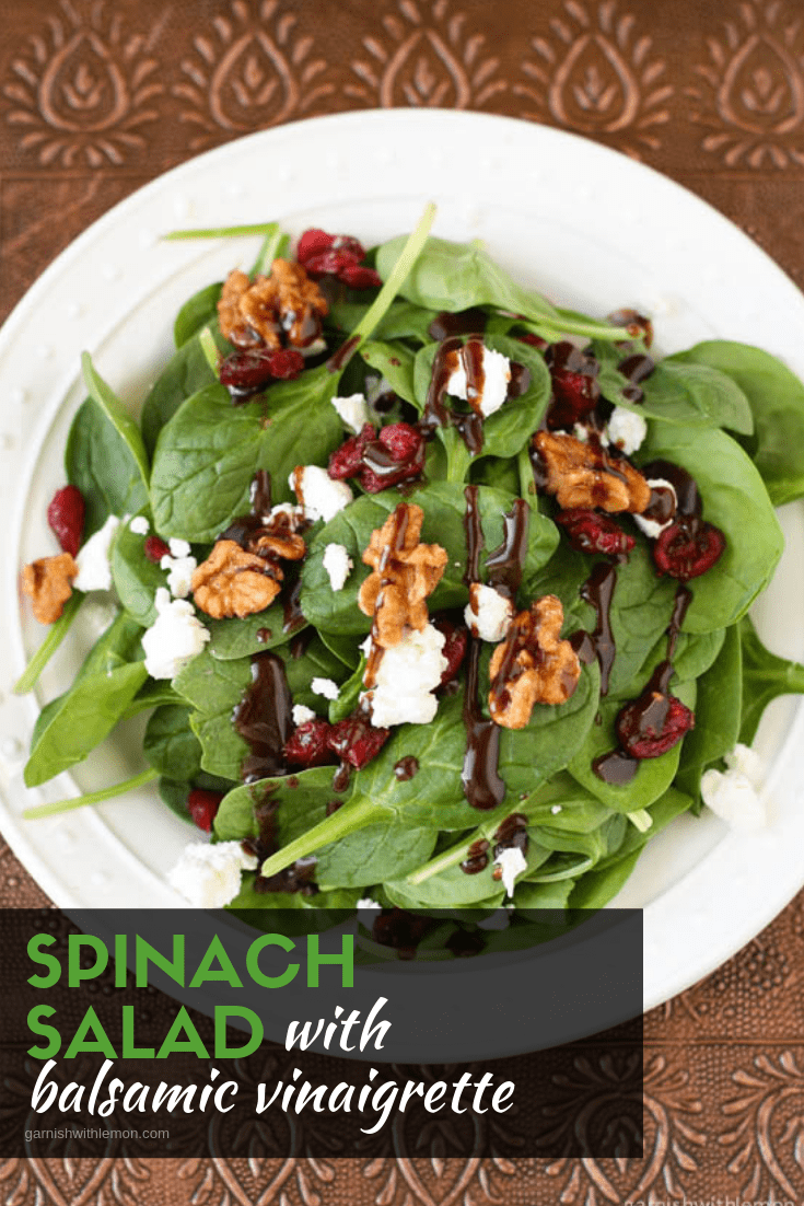 Top down image of spinach salad with balsamic vinaigrette on white plate.