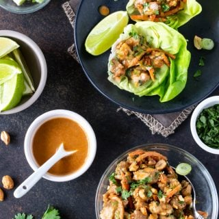 Top down image of Thai Peanut CHicken Lettuce Wraps recipe on a dark background with peanut sauce for dipping.