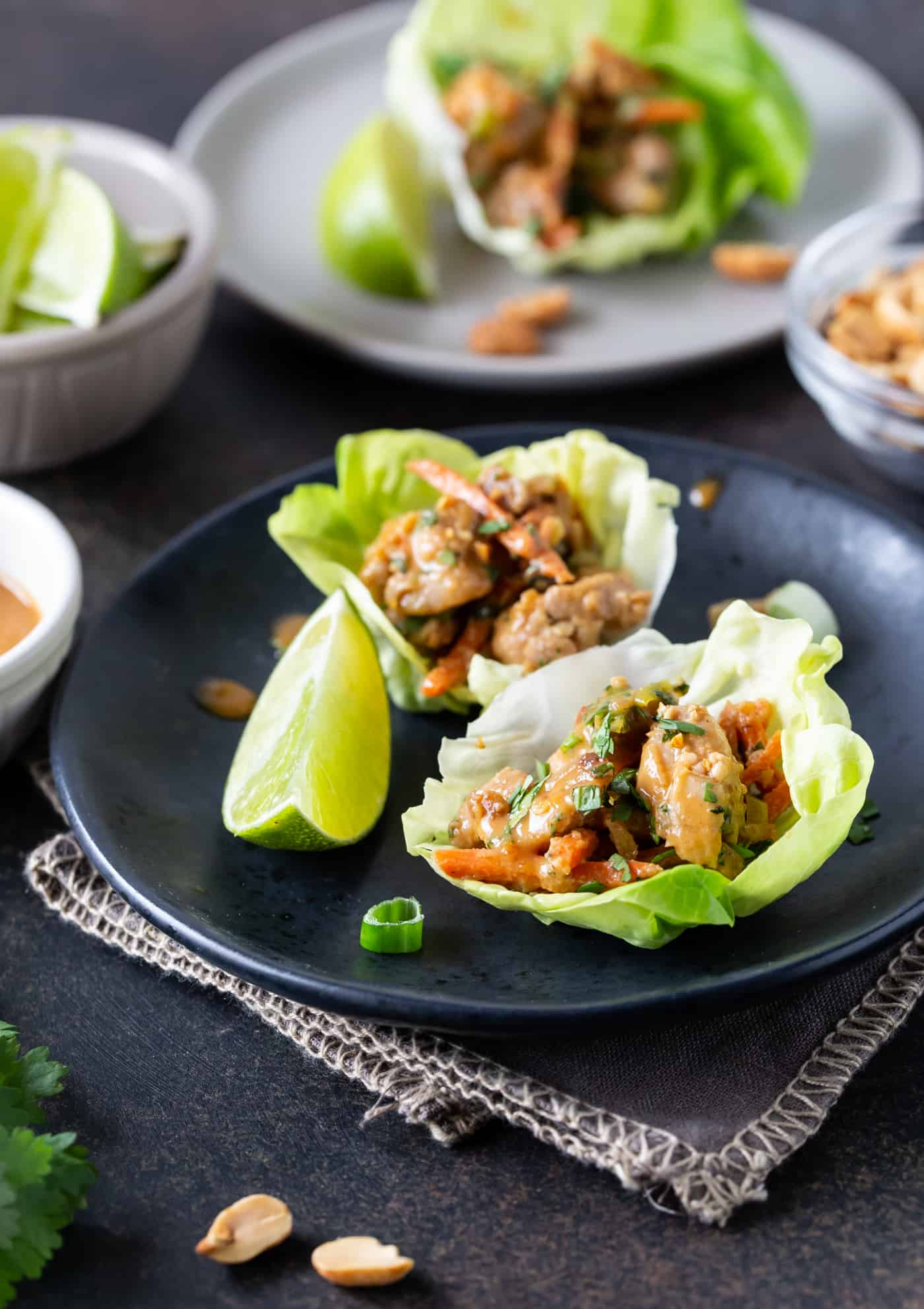 Image of Thai Peanut Chicken Lettuce Wraps Recipe on a dark plate with fresh lime wedges for garnish.