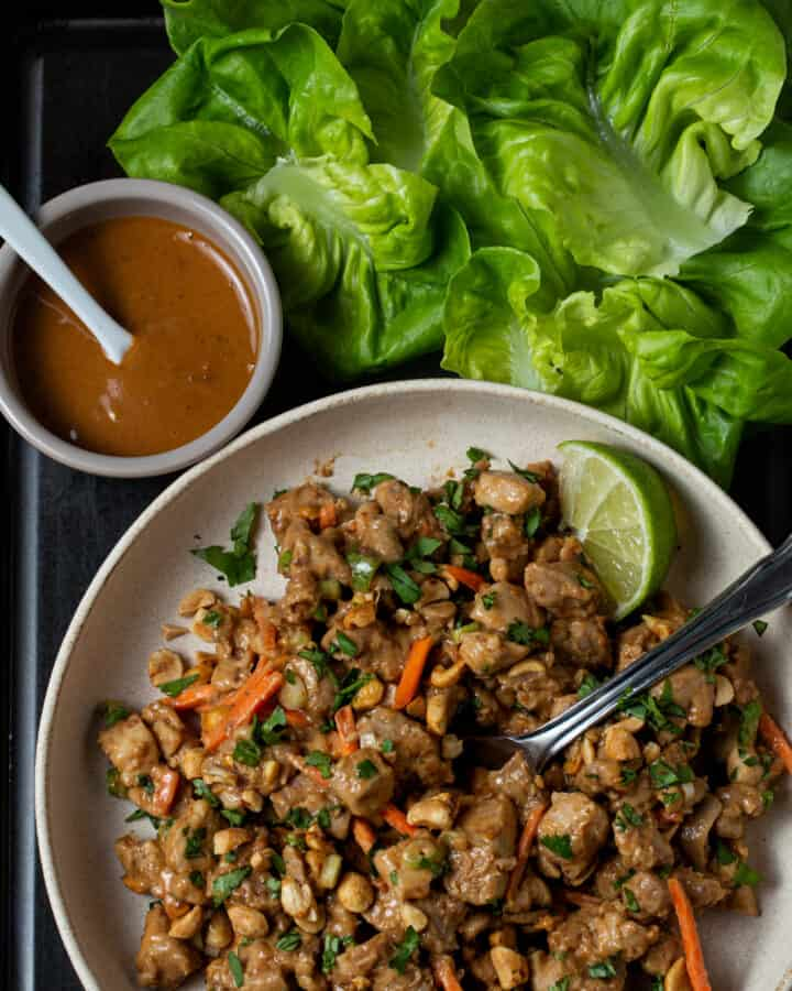 A bowl of  thai peanut chicken with lettuce cups.