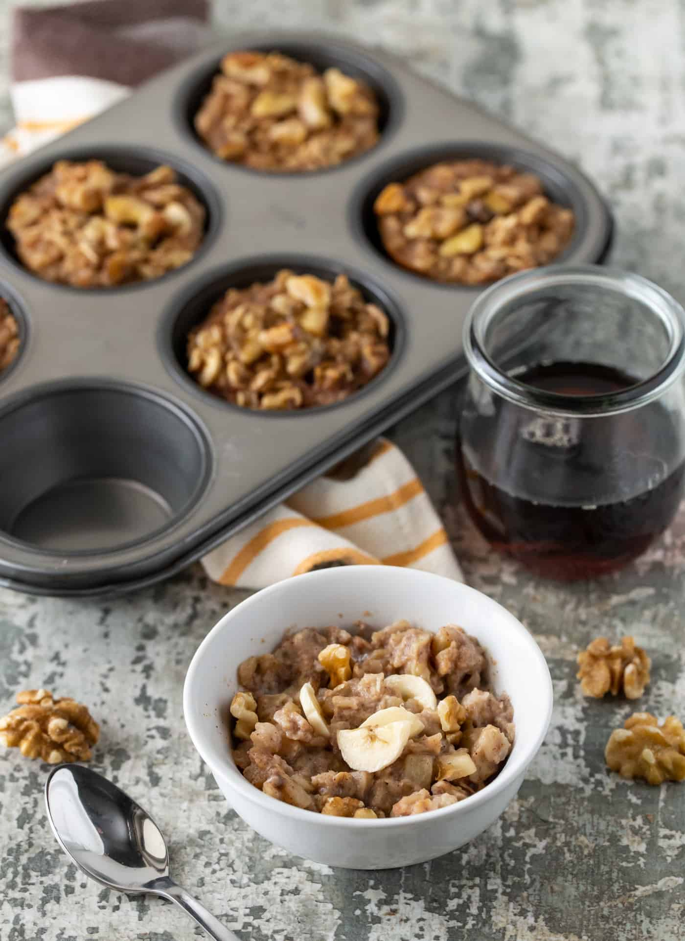 A white bowl filled with a Banana Nut Baked Oatmeal Cup. A muffin pan filled with Banana Nut Baked Oatmeal Cups is in the background along with a jar of maple syrup and walnuts.