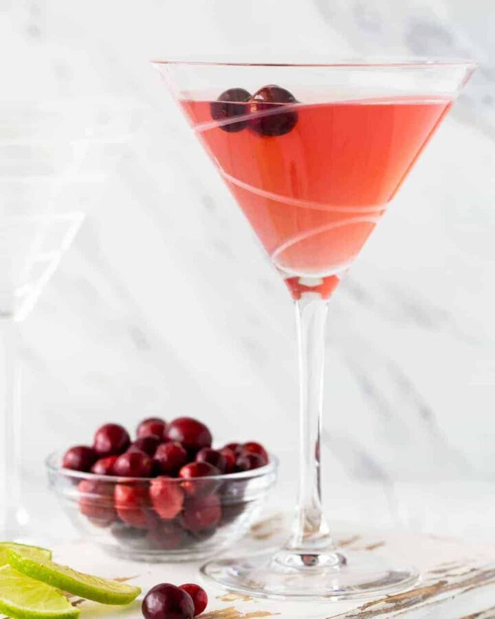 Straight on image of Metropolitan Cranberry Martini on a white background with fresh cranberries for garnish.