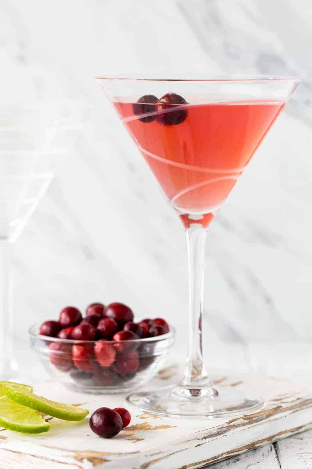 Straight on image of Metropolitan Cranberry Martini in glass with fresh lime wedges and cranberries for garnish.