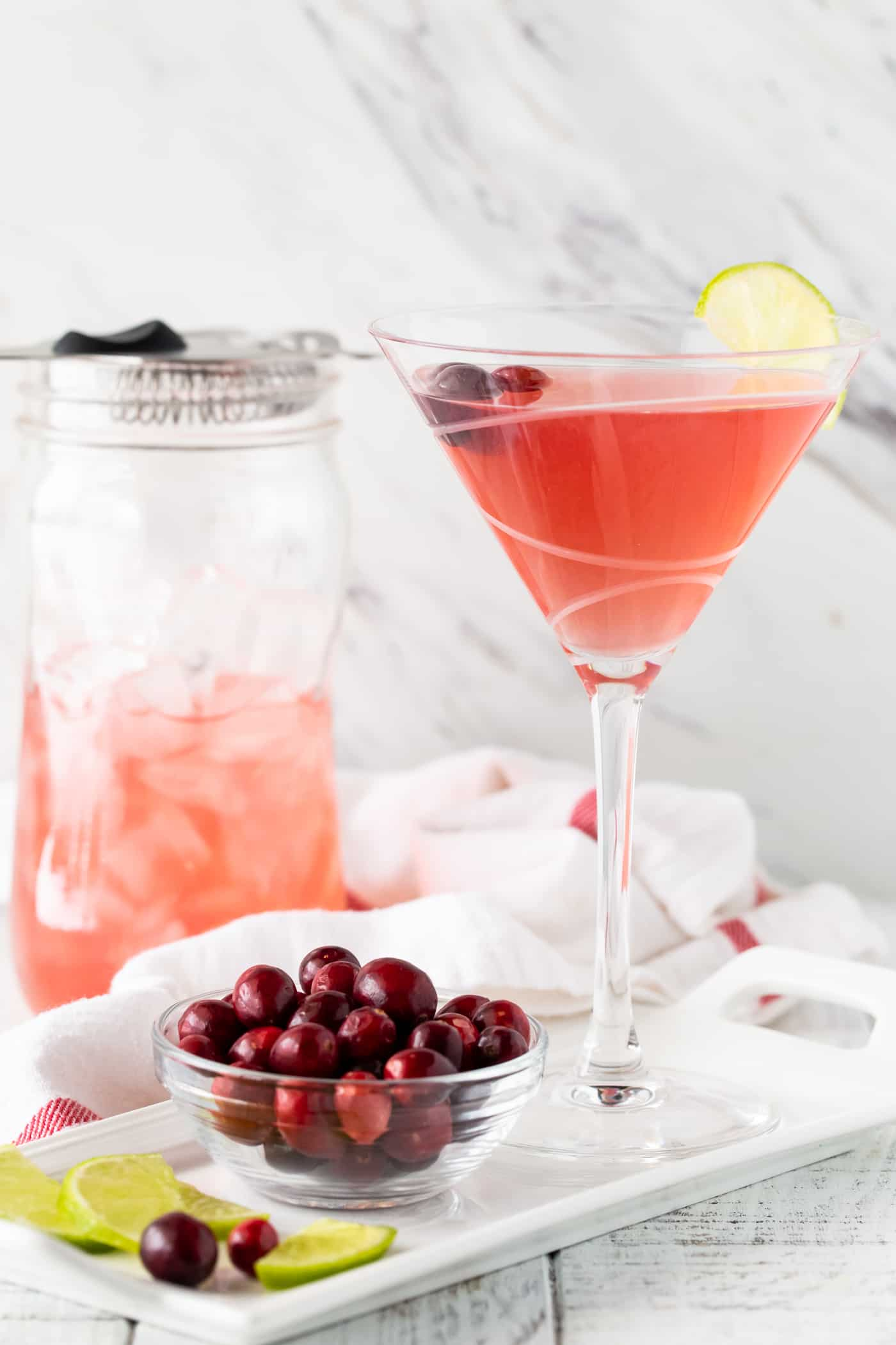 Straight on image of Metropolitan Cranberry Martini on a white background with a shaker in the background with fresh cranberries and lime wedges for garnish.