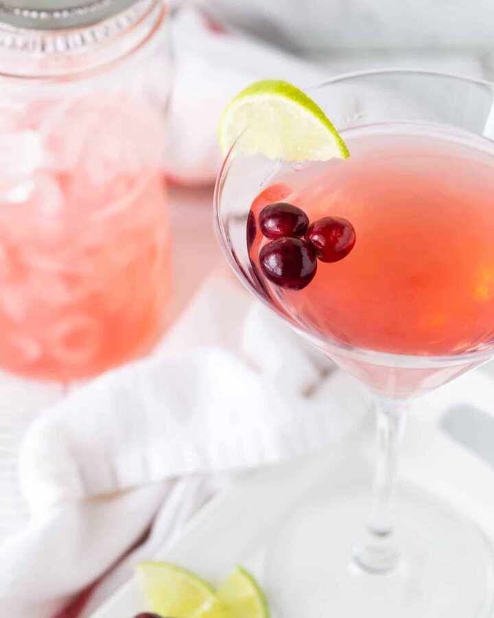 Metropolitan Cranberry Martini in tall glass on a white background with fresh cranberries and lime wedges for garnish.