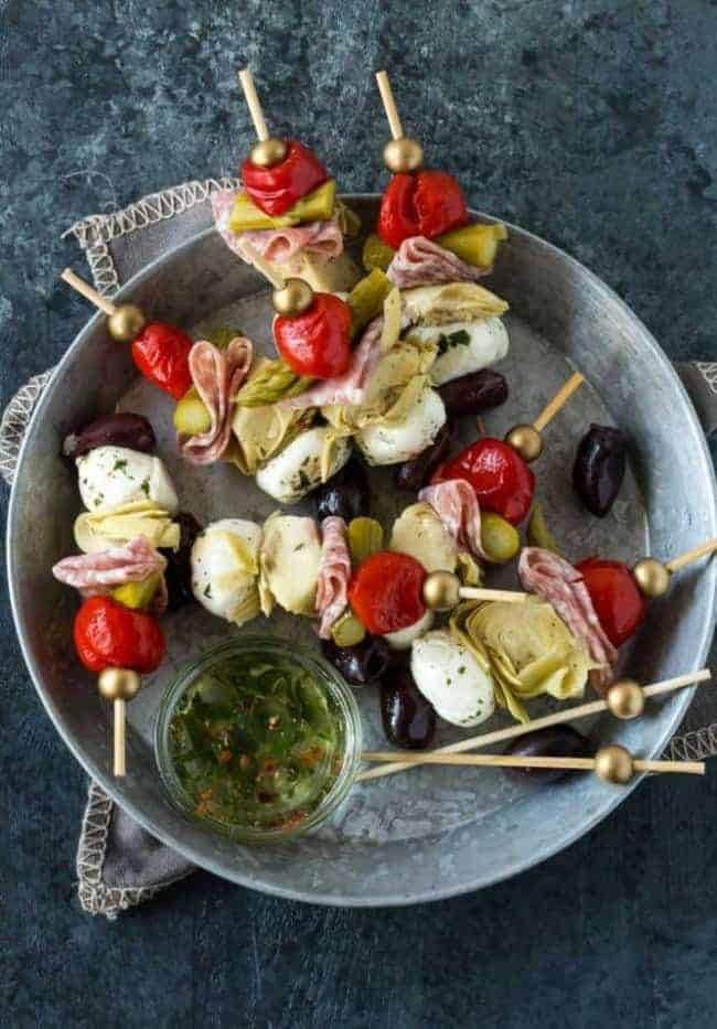 A bowl of antipasto skewers with dipping sauce.