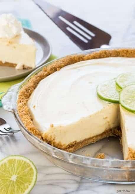 Key lime pie in a glass pie dish.