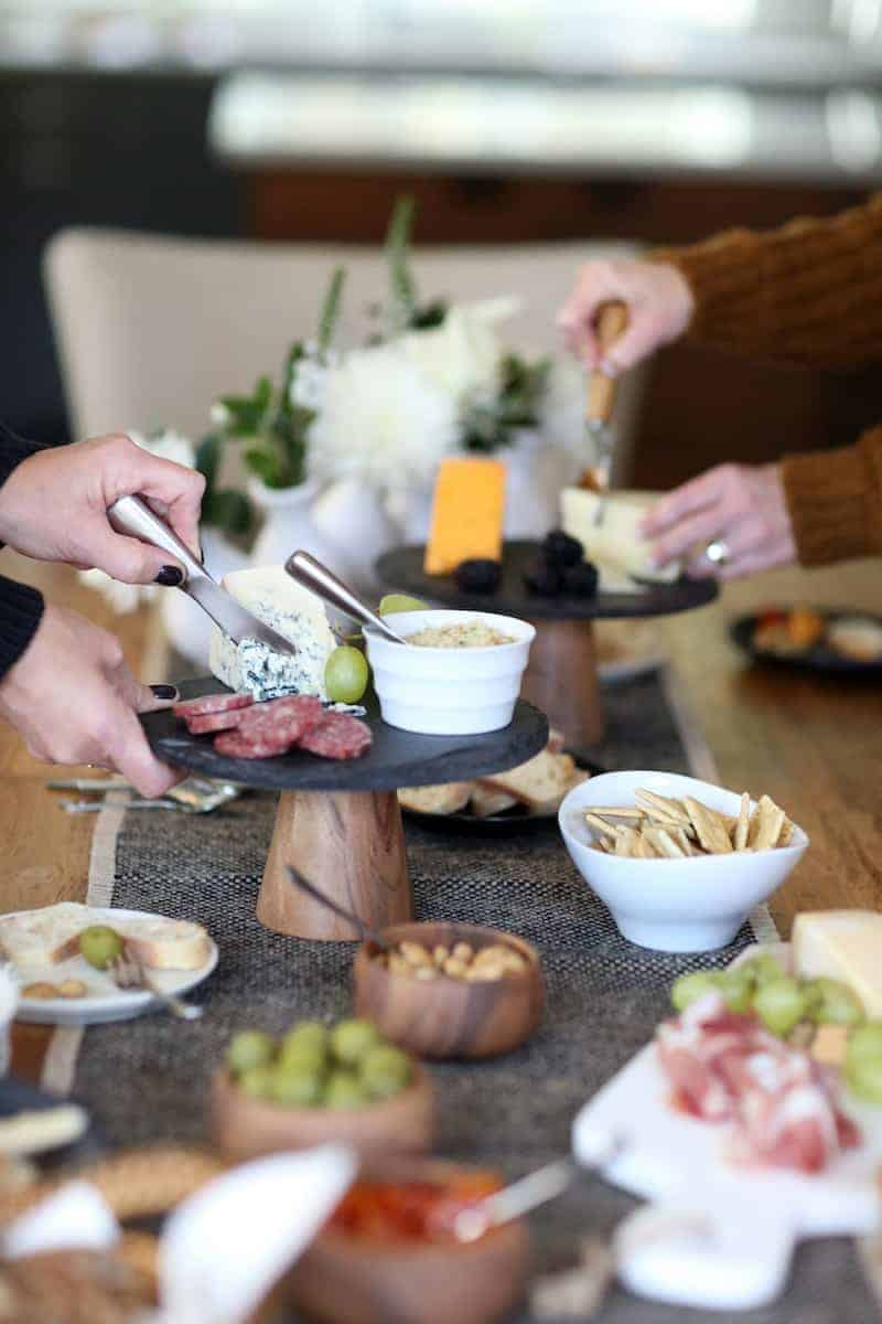 Hands cutting cheeses at a table with a plates of food with Garnish and Lemon.