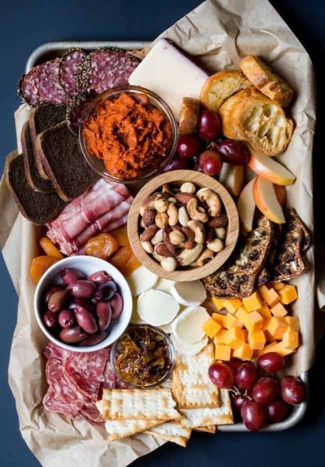 A tray of meats, cheeses, and fruits on a table.