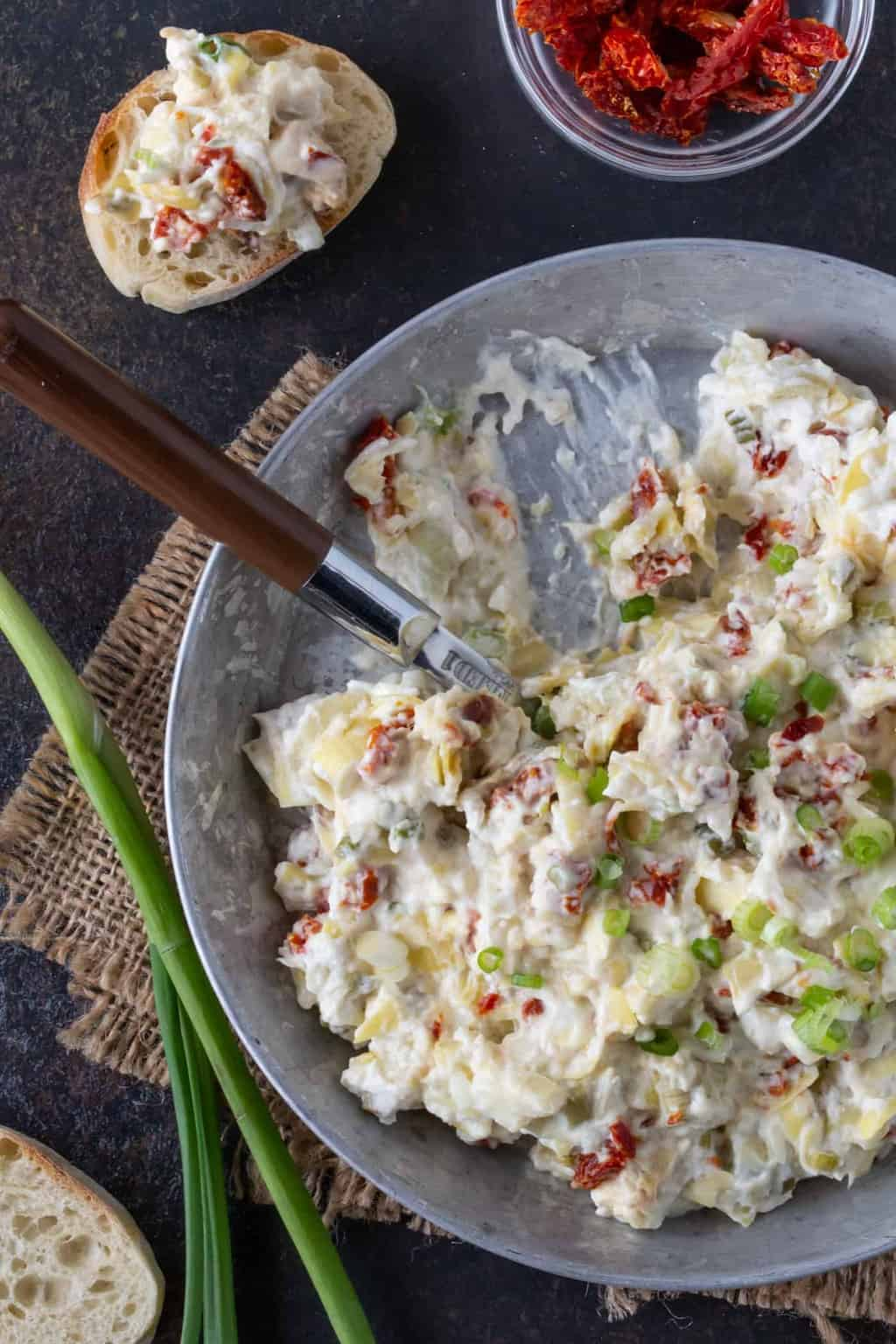 Top down image of Asiago Dip recipe on a metal pie plate with green onions for garnish.