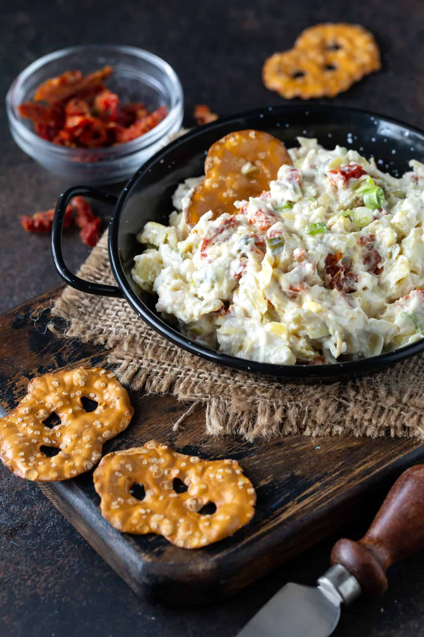 Asiago Dip in a black serving dish, garnished with green onions and serves with pretzels for dipping.