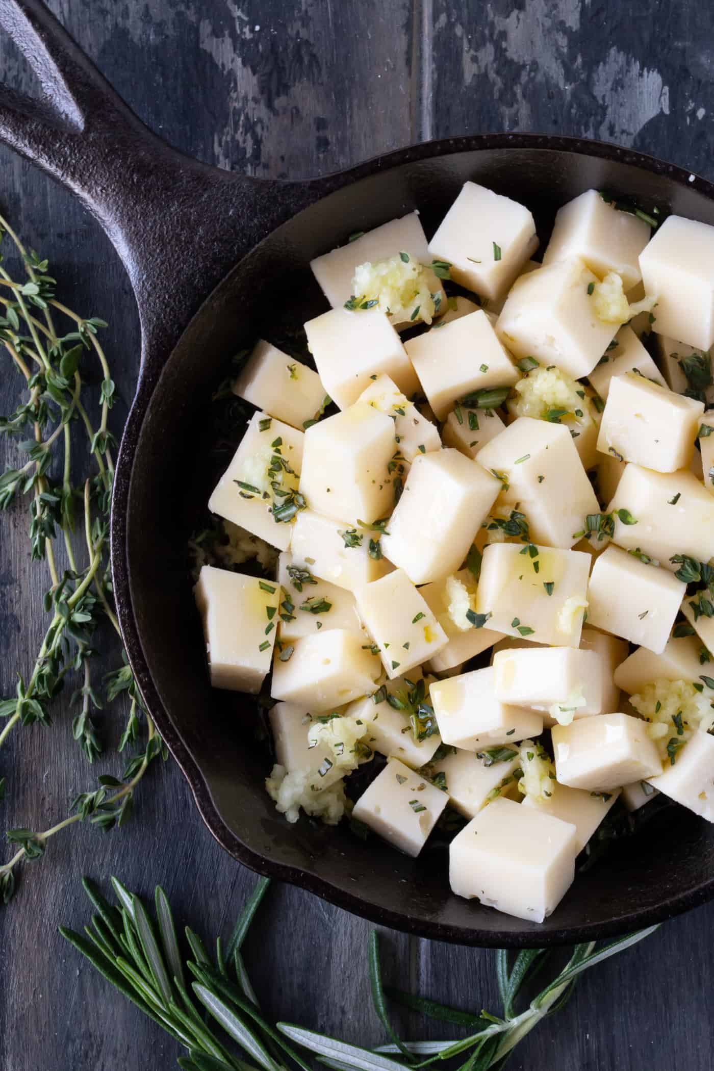 Cubed Fontina Cheese in a small black cast iron pan with fresh herbs, garlic and olive oil.