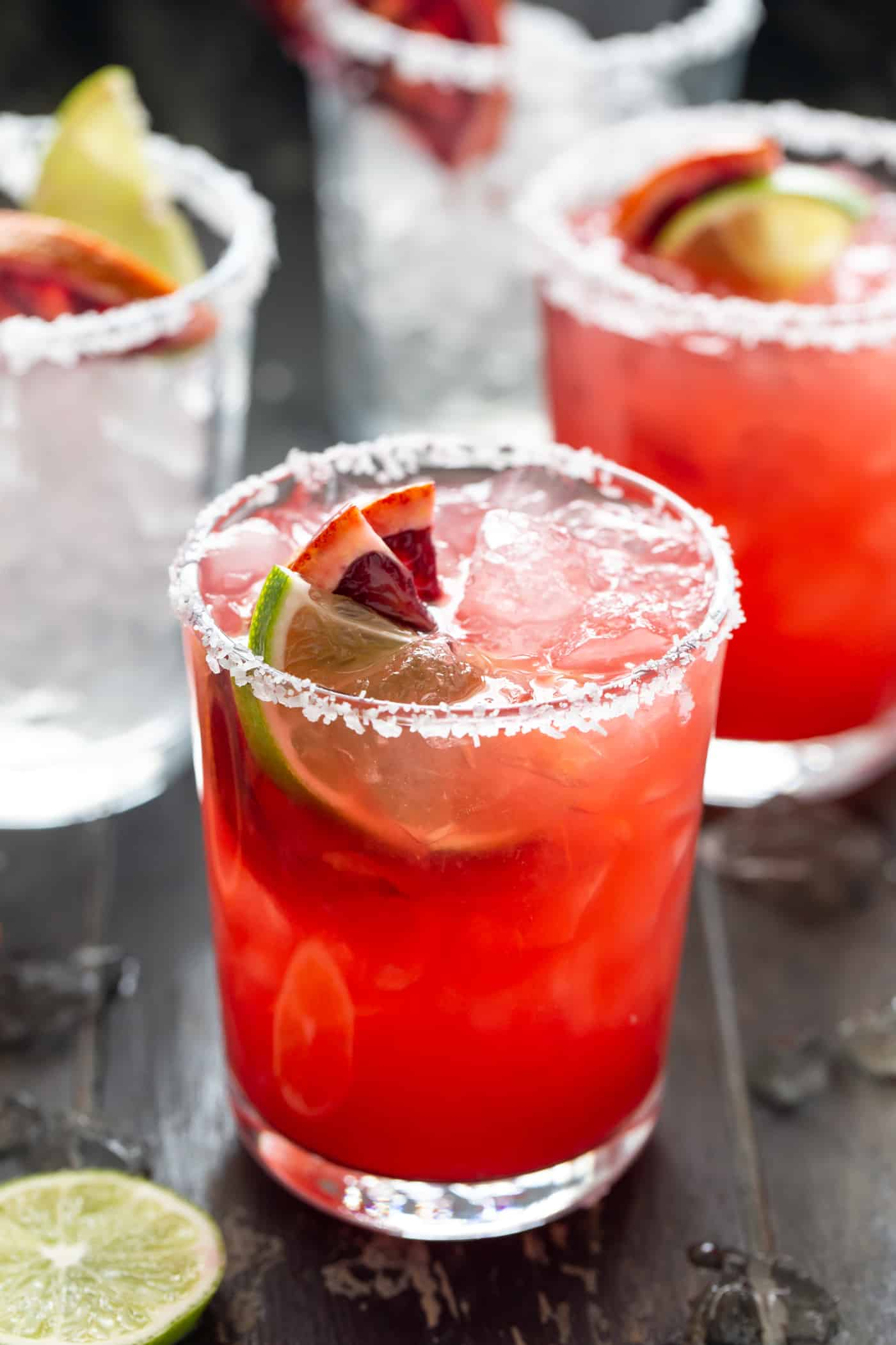 Lowball glasses filled with Blood Orange Margaritas. Garnished with a salt rim and fresh lime and blood orange slices.
