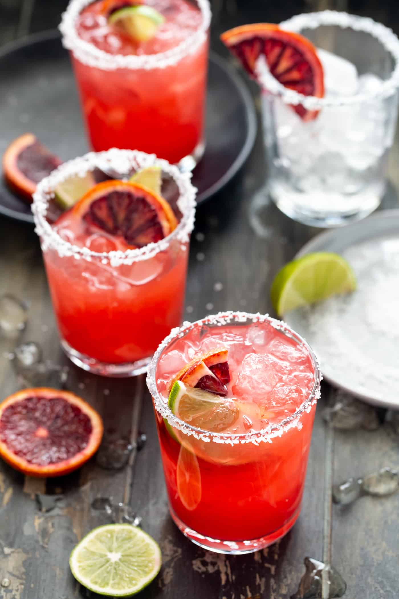 Glasses filled with Blood Orange Margaritas and garnished with fresh lime and blood orange slices. A gray plate filled with salt for the glass rims is nearby.