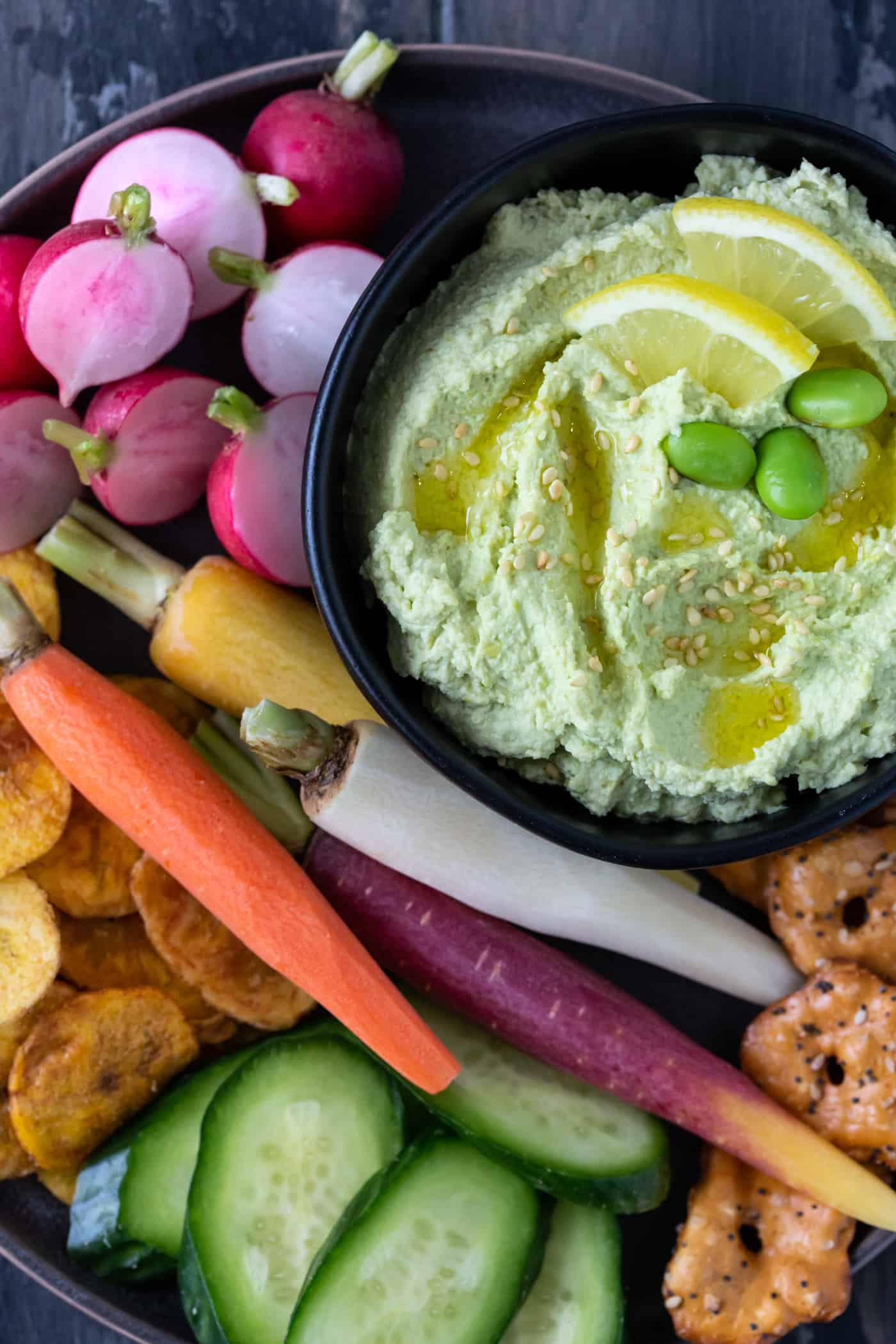 Black bowl of homemade edamame hummus recipe surrounded by fresh vegetables.