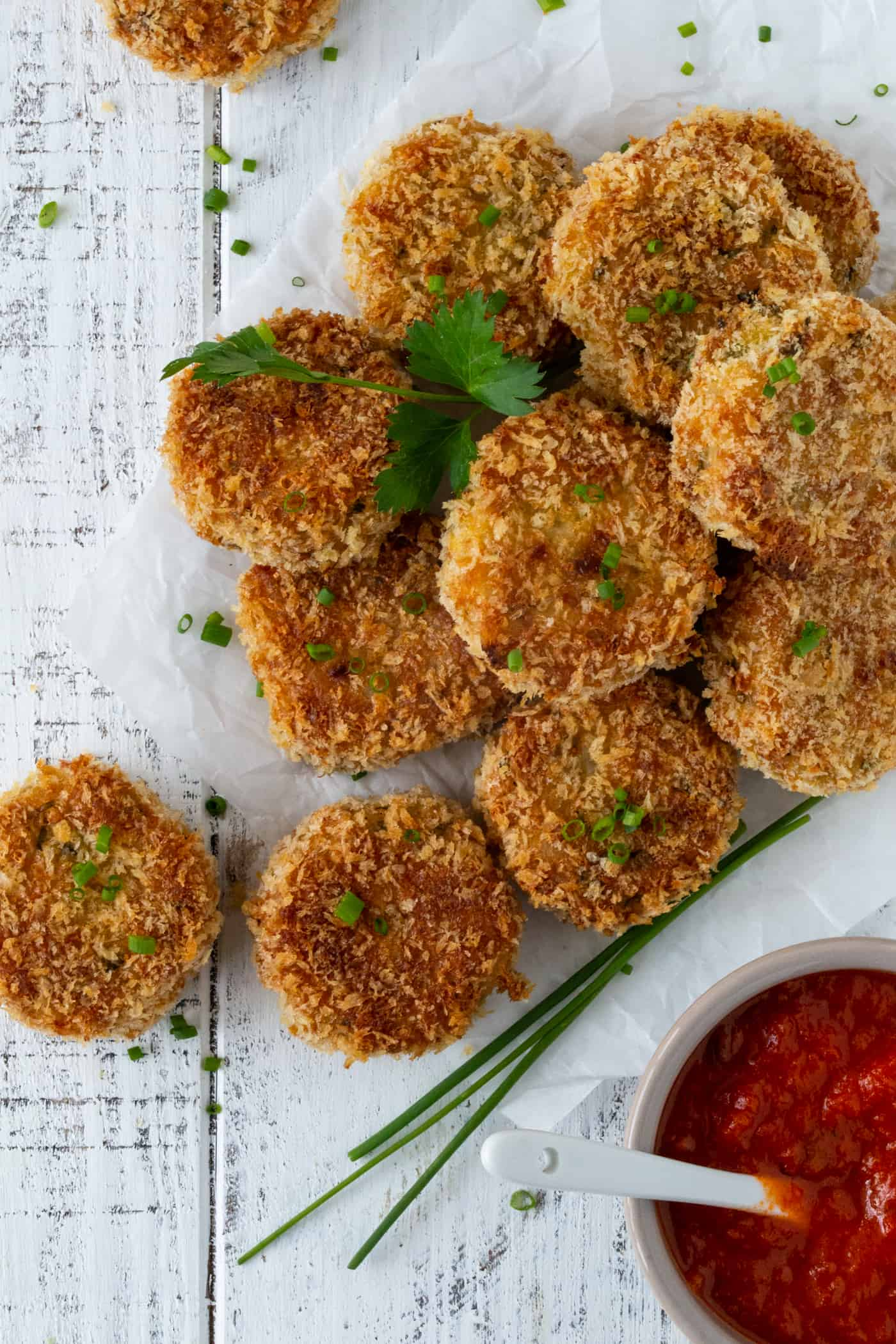 Pile of Cakes on white parchment paper and garnished with fresh chives, grated parmesan cheese and chunky marinara sauce.