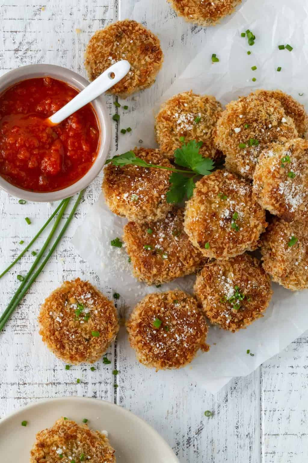 Fontina Chive Risotto Cakes scattered on white parchment paper and garnished with chopped chives and parmesan cheese. A bowl of marinara sauce is next to the risotto cakes.