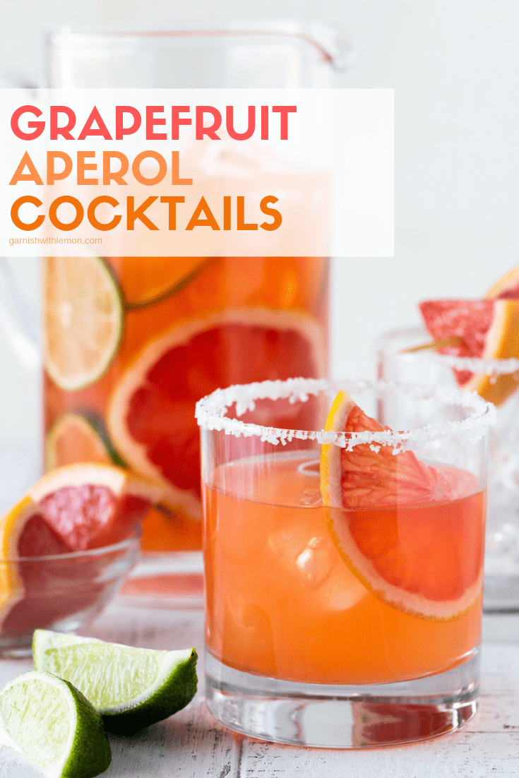 Grapefruit Aperol Cocktails in a pitcher and a low ball glass with a salt rim on a white background.