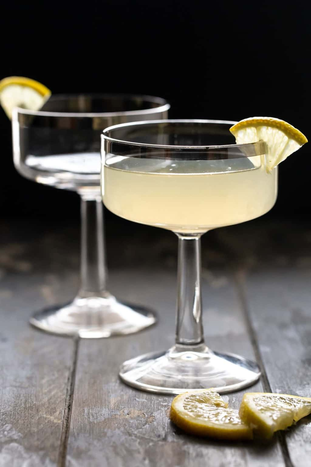 Ginger Pear Martini recipe in a coupe glass with a silver rim on a dark background.