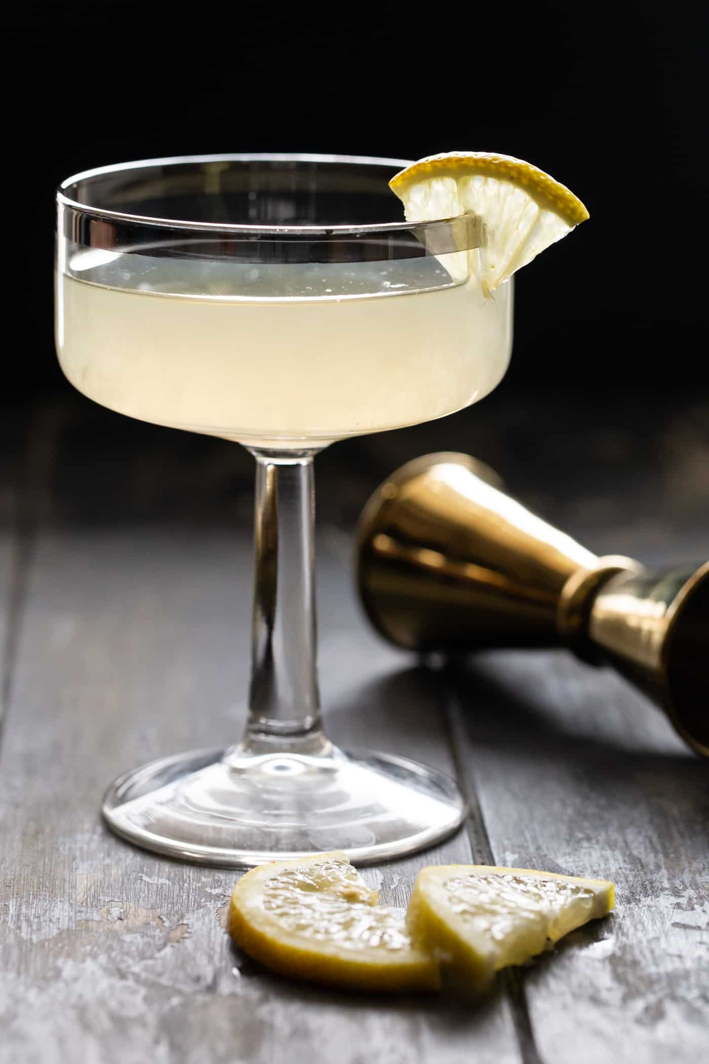 COupe glass filled with Ginger pear Martini recipe and garnished with a small lemon slice. Ona dark background with a gold jigge.
