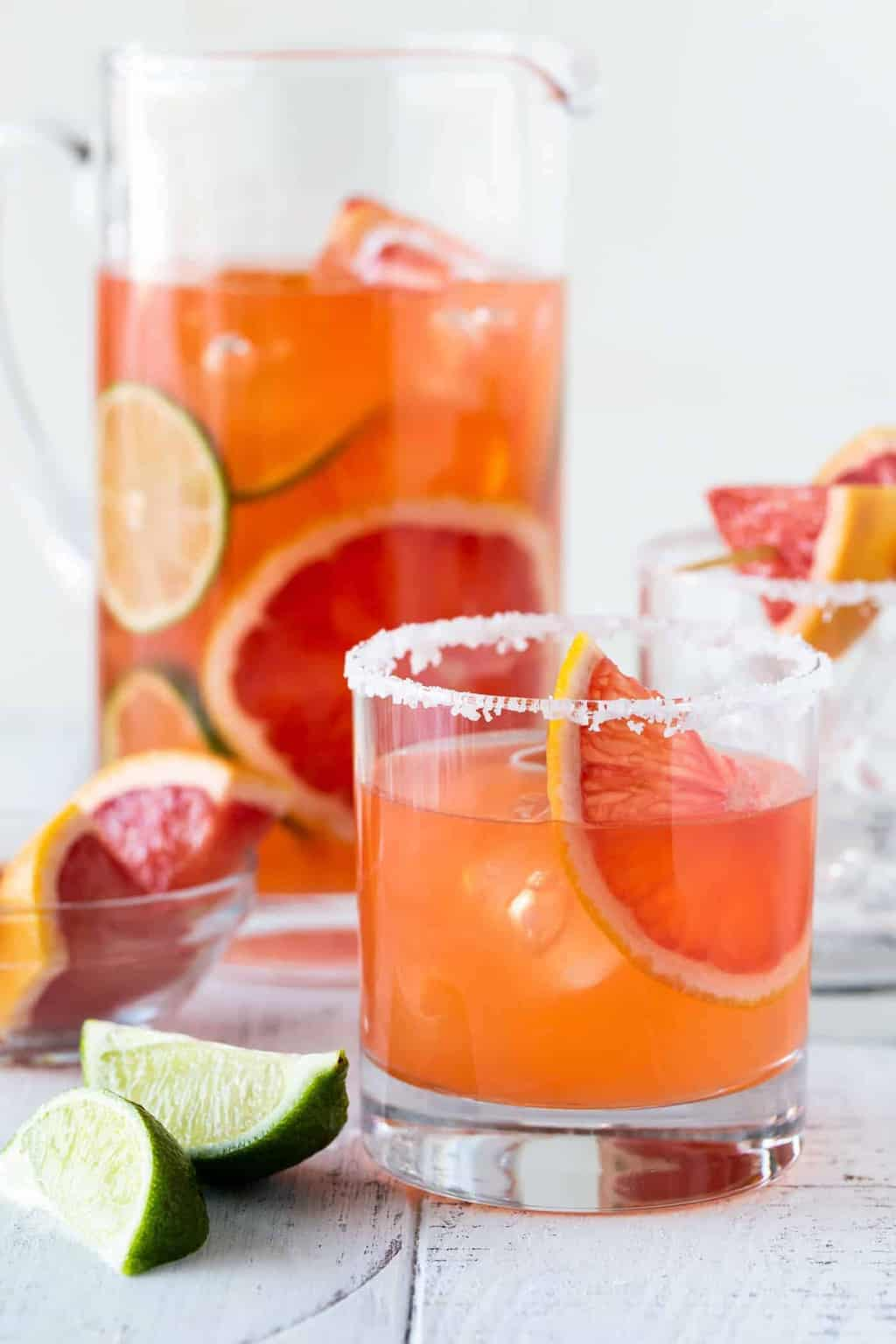 Graperfuit Aperol Cocktails in a low ball glass with a salt rim. Pitcher of Grapefruit Aperol cocktails with fresh grapefruit slices.