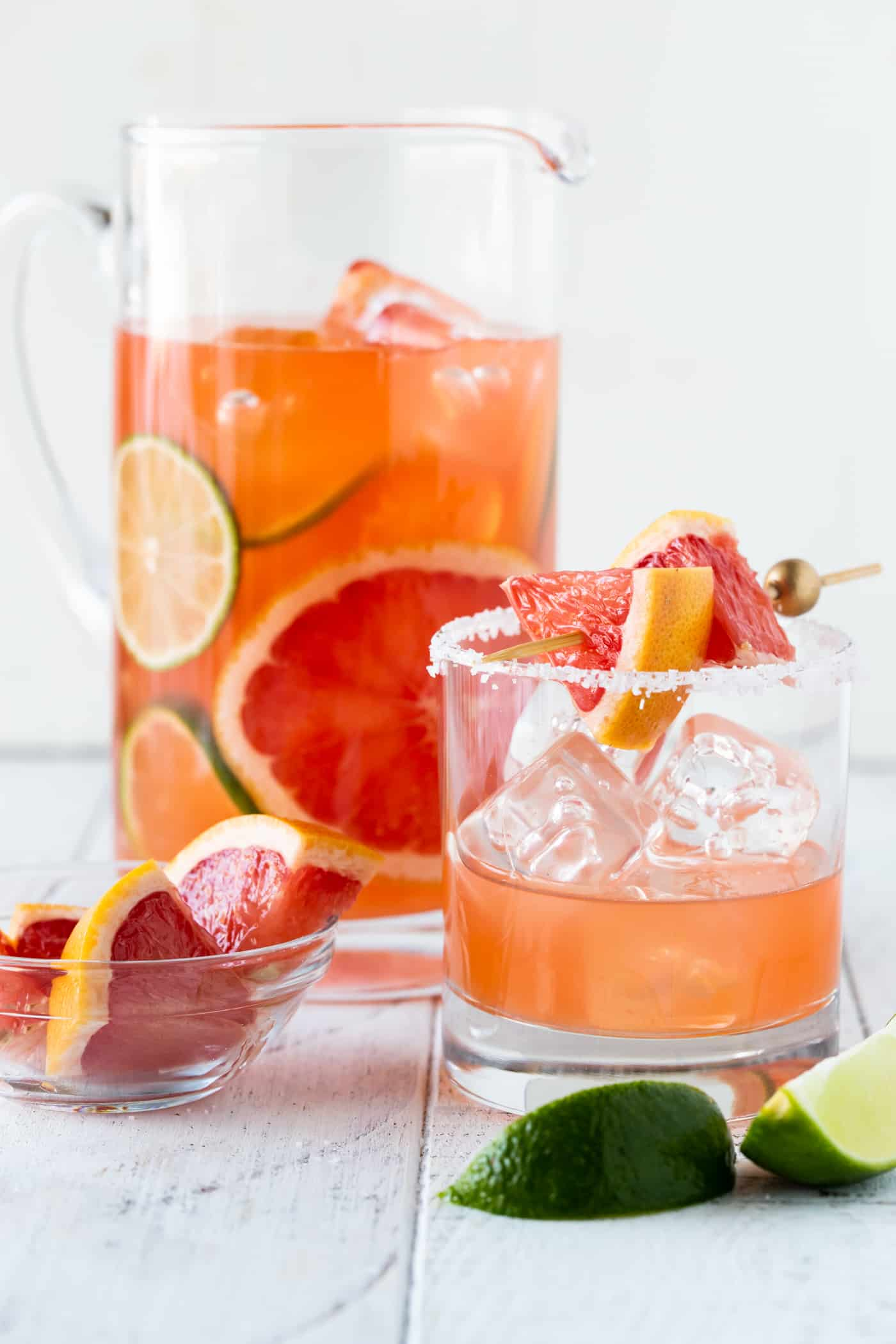 Grapefruit Aperol Cocktails in a low ball salt rimmed glass with grapefruit. pitcher of grapefruit aperol cocktails on white background.