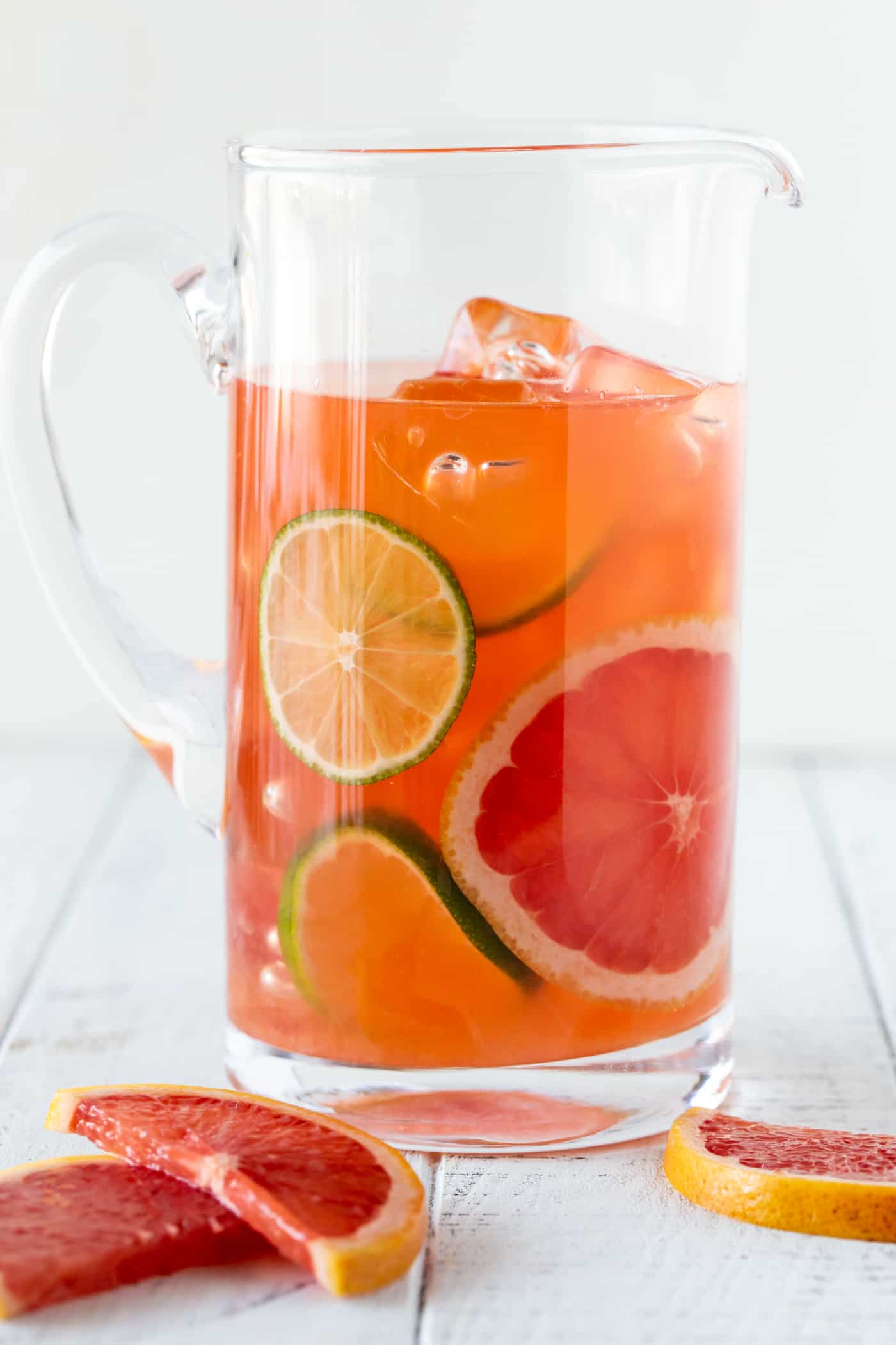 Glass pitcher filled with Grapefruit Aperol Cocktails garnished with fresh grapefruit and limes slices.
