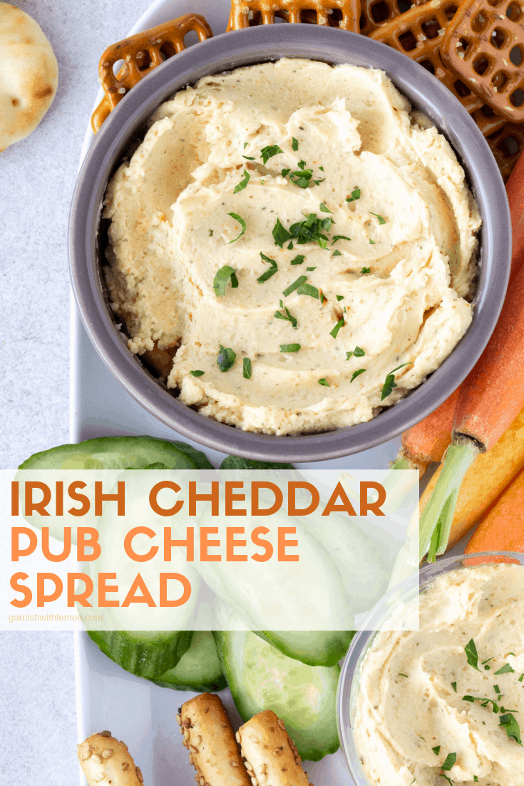 Irish Cheddar Pub Cheese Spread in small bowls surrounded by carrots, sliced cucumbers, breadsticks and crackers.