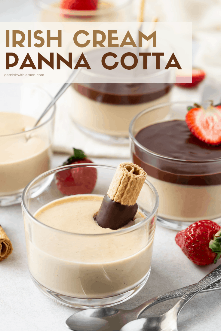 Glass ramekins filled with Irish Cream Panna Cotta. Garnished with fresh sliced strawberry halves, chocolate ganache and chocolate dipped wafer cookies.
