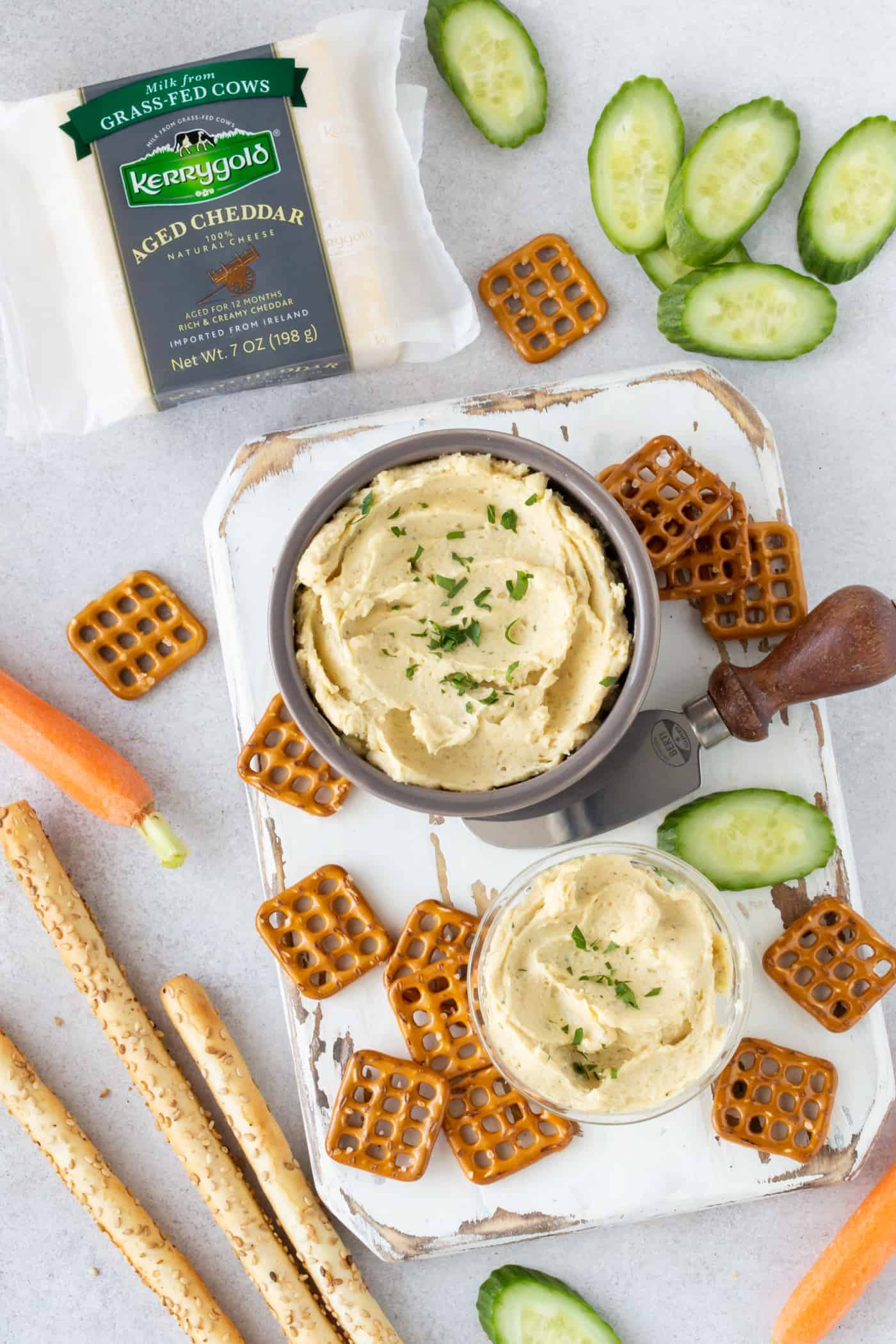Small bowls of Irish Cheddar Pub Cheese surrounded by fresh cucumbers, carrots, crunchy breadsticks and pretzels.
