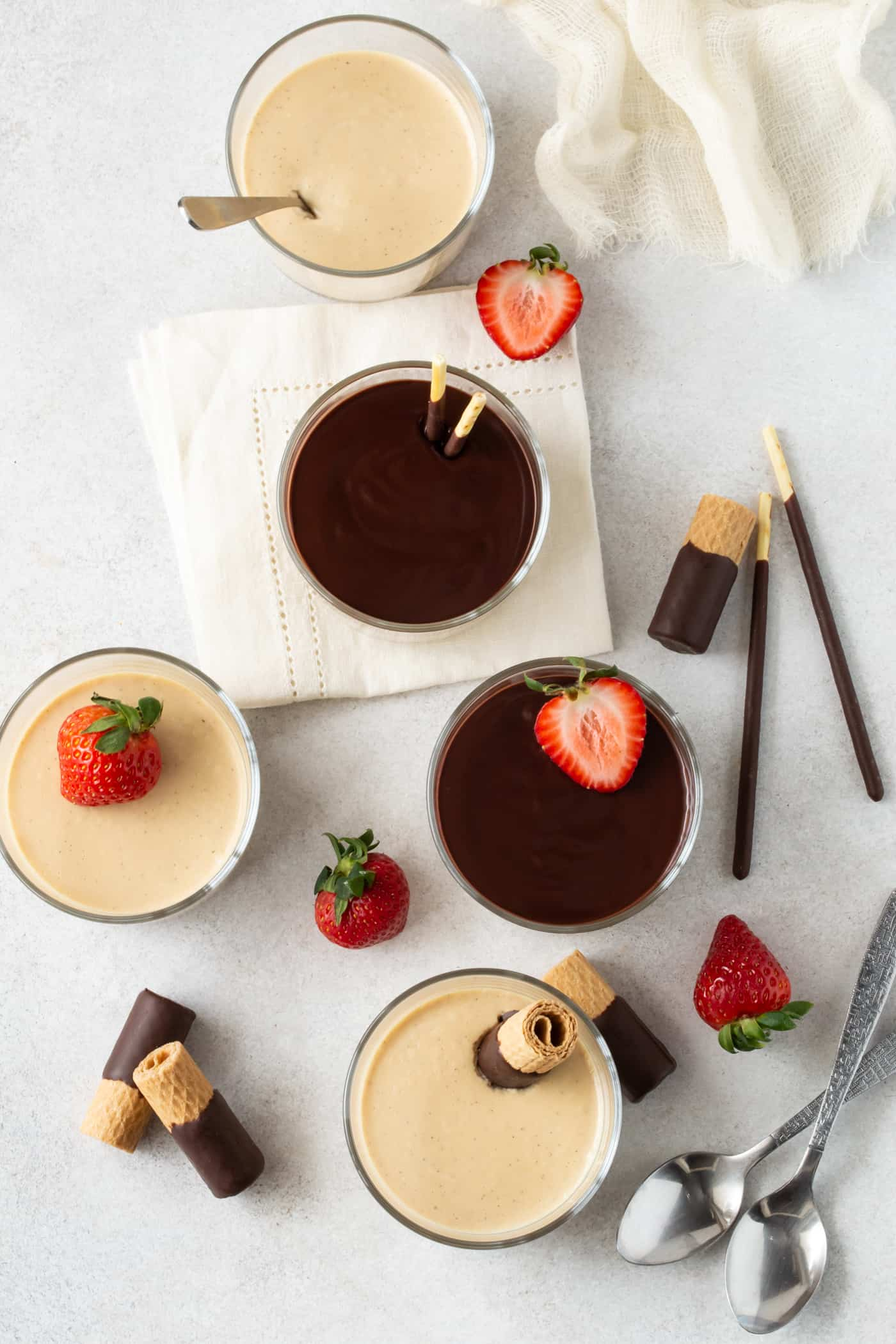 Top down shot of Irish Cream Panna Cotta in glass ramekins. Garnished with chocolate ganache, fresh strawberries and chocolate covered wafer cookies.