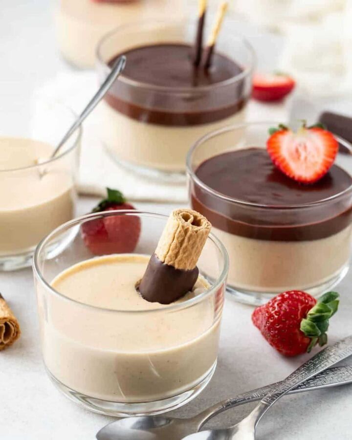 Glass ramekins of Irish Cream Panna Cotta garnished with chocolate ganache, sliced strawberries and chocolate covered wafer cookies.