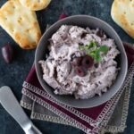 Gray bowl of Kalamata Olive Cream Cheese Spread, with olives, fresh parsley and mini naan breads.