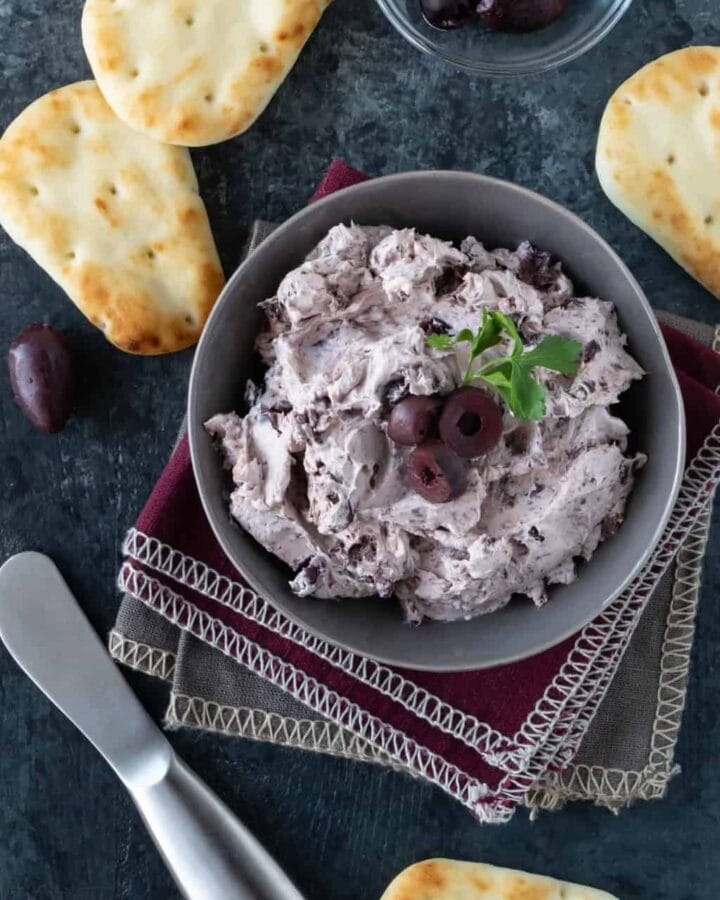 Gray bowl of Kalamata Olive Cream Cheese Spread. Garnished with olives, fresh parsley and mini naan breads.
