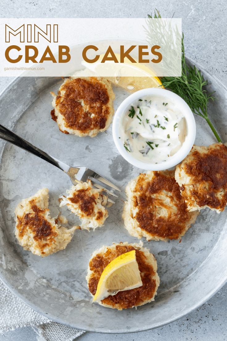 Top down image of mini crab cakes on a silver tray with lemon wedges and aioli for dipping.