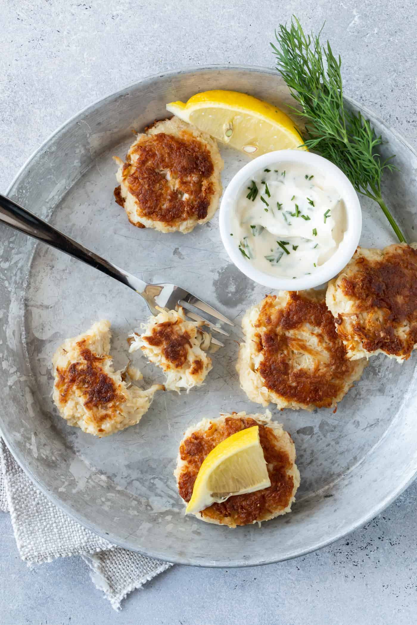 Mini Crab Cakes on a silver tray with  dill aioli and fresh lemon wedges for garnish.