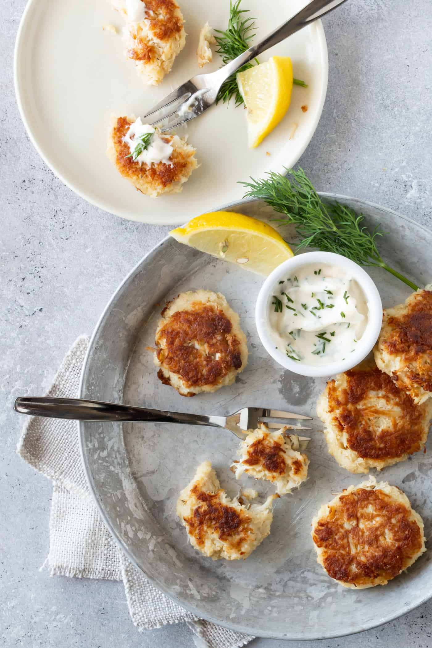 Mini crab cakes on a silver plate with a small fork for eating and dill aioli and fresh lemon for garnishes.