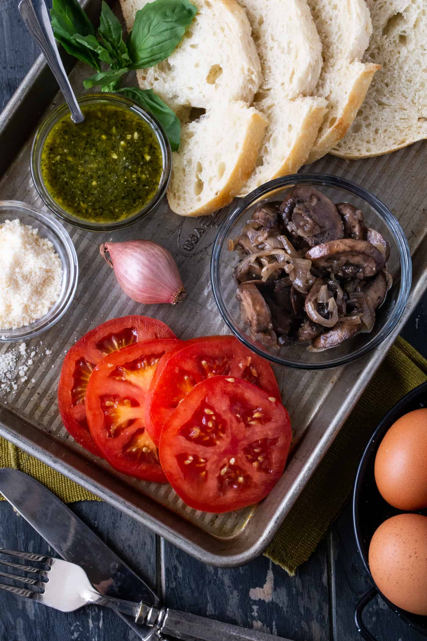 Ingredients for Open-Faced Mushroom and Fried Egg Sandwiches on a sheet pan. Ingredients include bread slices, sauteed mushrooms, shallots, parmesan cheese, pesto and sliced bread.