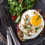 An open-faced Mushroom and Fried Egg Sandwich on a dark gray plate with a side salad.