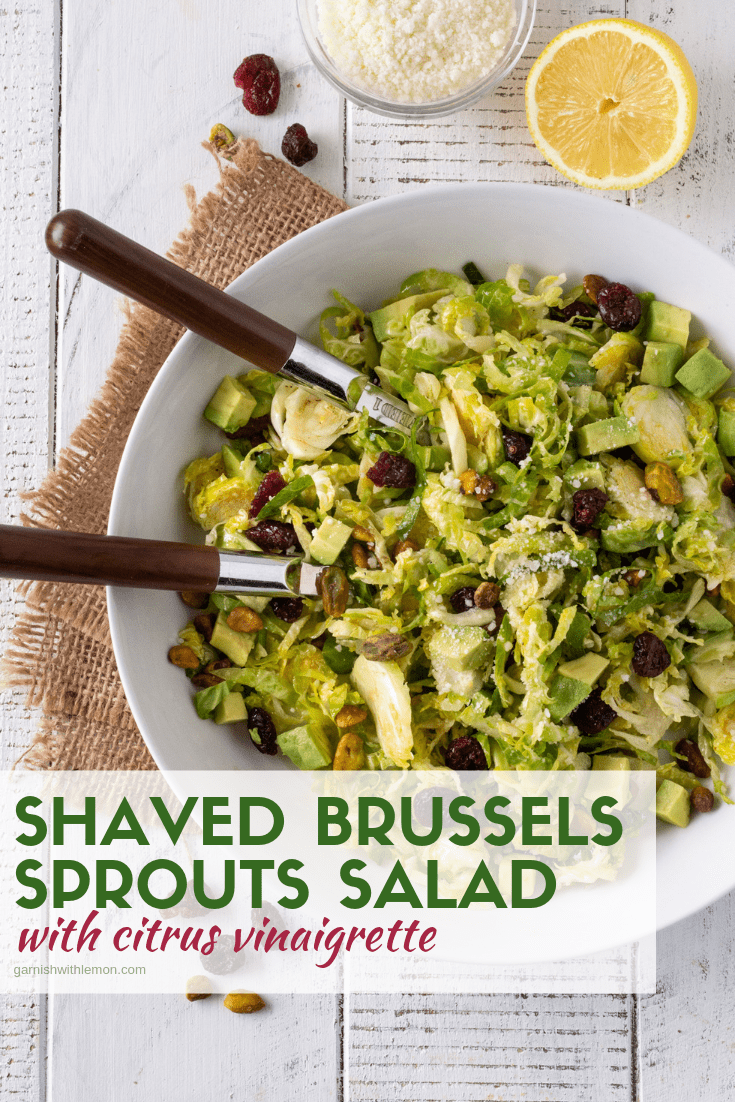 White bowl filled with Shaved Brussels Sprouts Salad recipe with a tangy Citrus Vinaigrette.