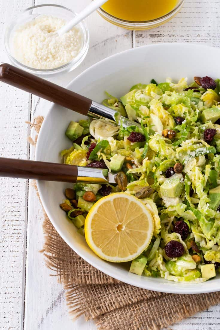 Large white bowl filled with Shaved Brussels Sprouts Salad with a zesty Citrus Vinaigrette. Garnished with avocado, dried cranberries, Pecorino cheese and pistachios.