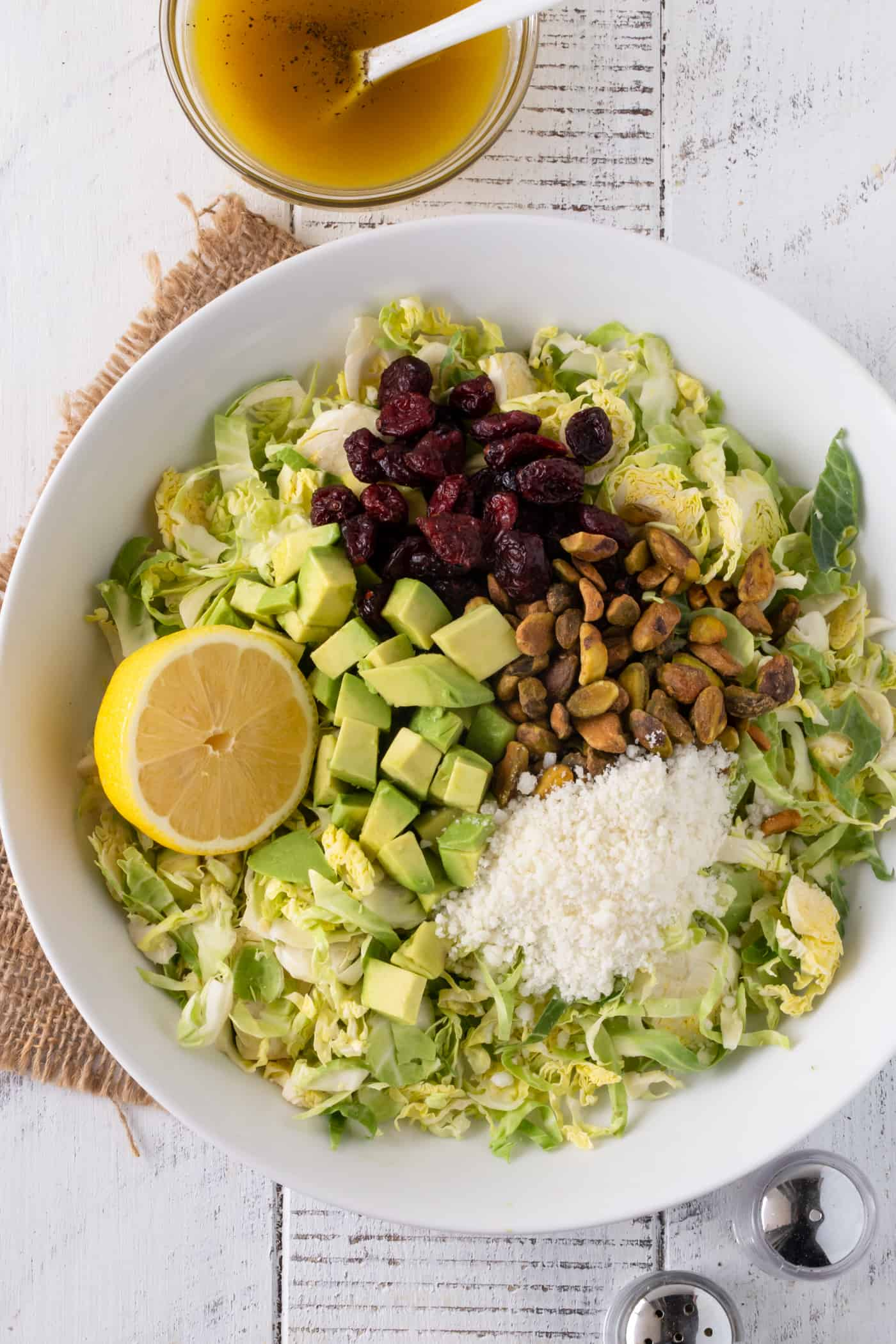 A deconstructed Shaved Brussels Sprouts Salad with Citrus Vinaigrette in a white bowl. Garnished with fresh avocado, dried cranberries, Pecorino cheese and pistachios.